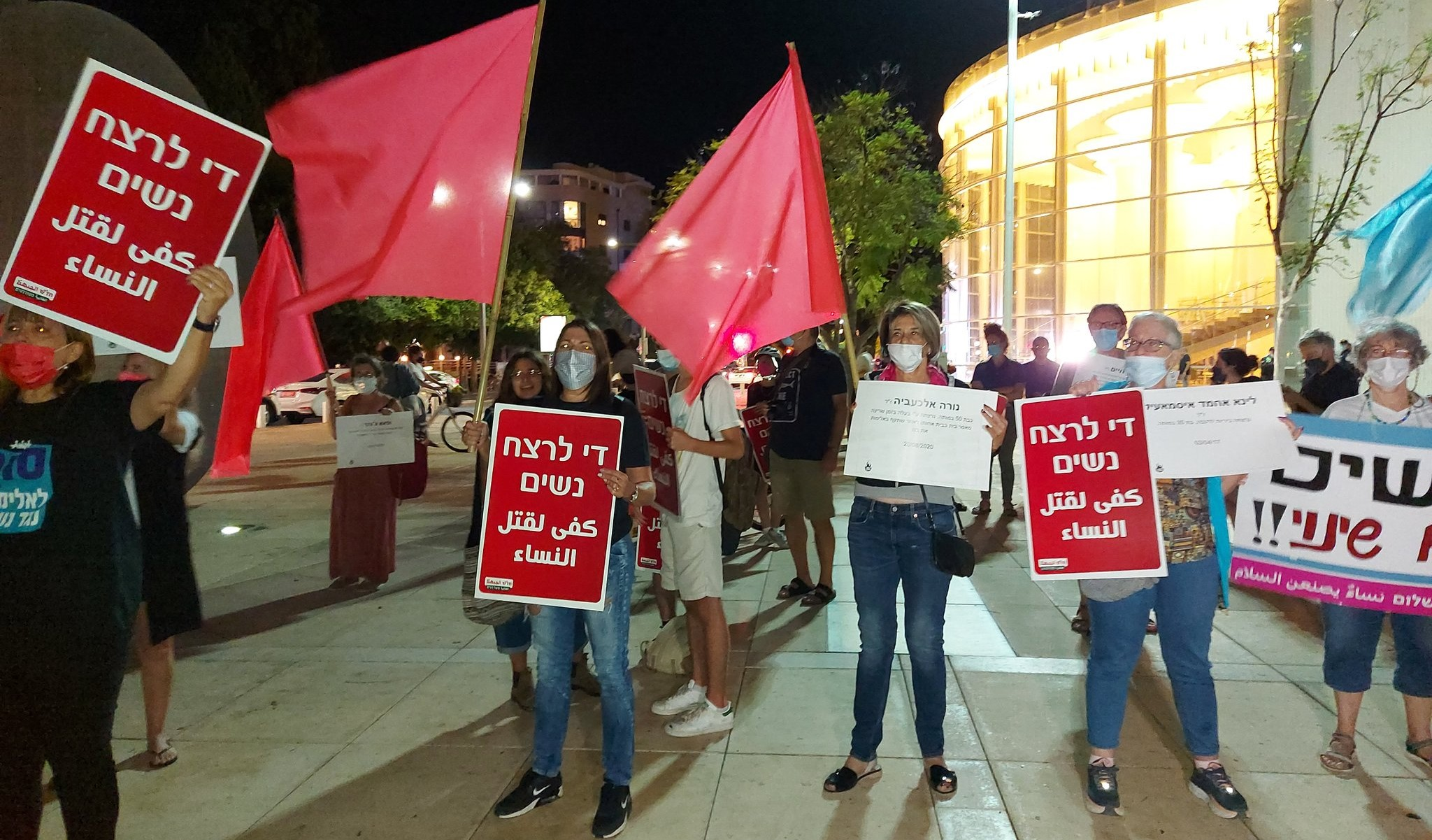 """Demonstrators protest violence women at Habima Square in Tel Aviv, Wednesday October 22. The red Hadash placards read """"Enough murder of women."""""""