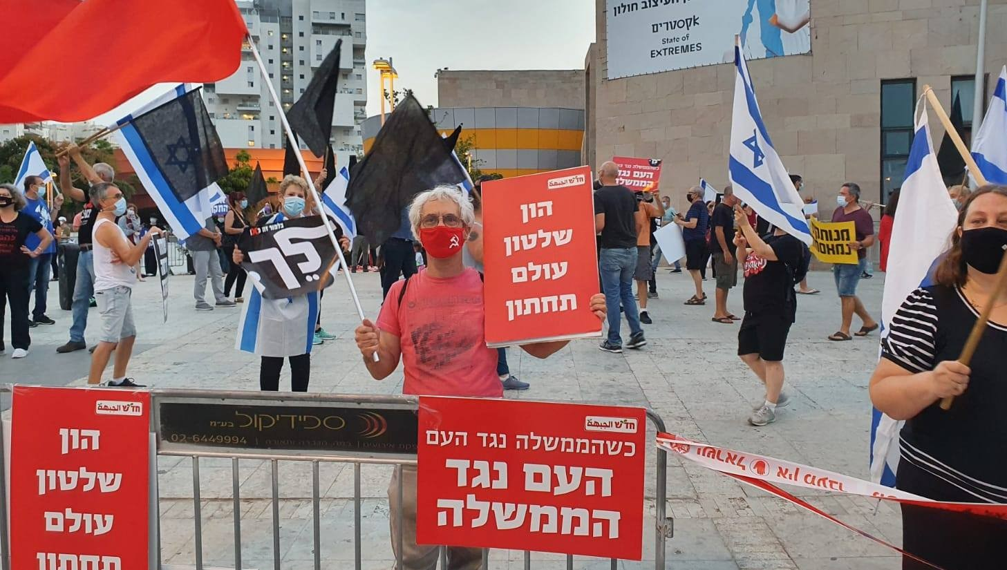 "Demonstrators protest near the Mediatheque in Holon, last Saturday, October 24. The Hadash placard held by a Communist demonstrator reads: ""Capital, Rule, and the Criminal Underworld""; the sign on the fence in front of him reads: ""When the government is against the people, the people are against the government."""