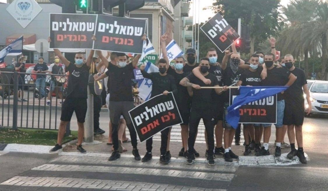 """Members of the La Familia gang brandish a blue Likud flag and placards reading """"Leftists are traitors"""" and """"Leftists, go with them"""" [i.e., leave with the Arabs] opposite an anti-Netanyahu demonstration in Rabin Square, Tel Aviv, October 17, 2020."""