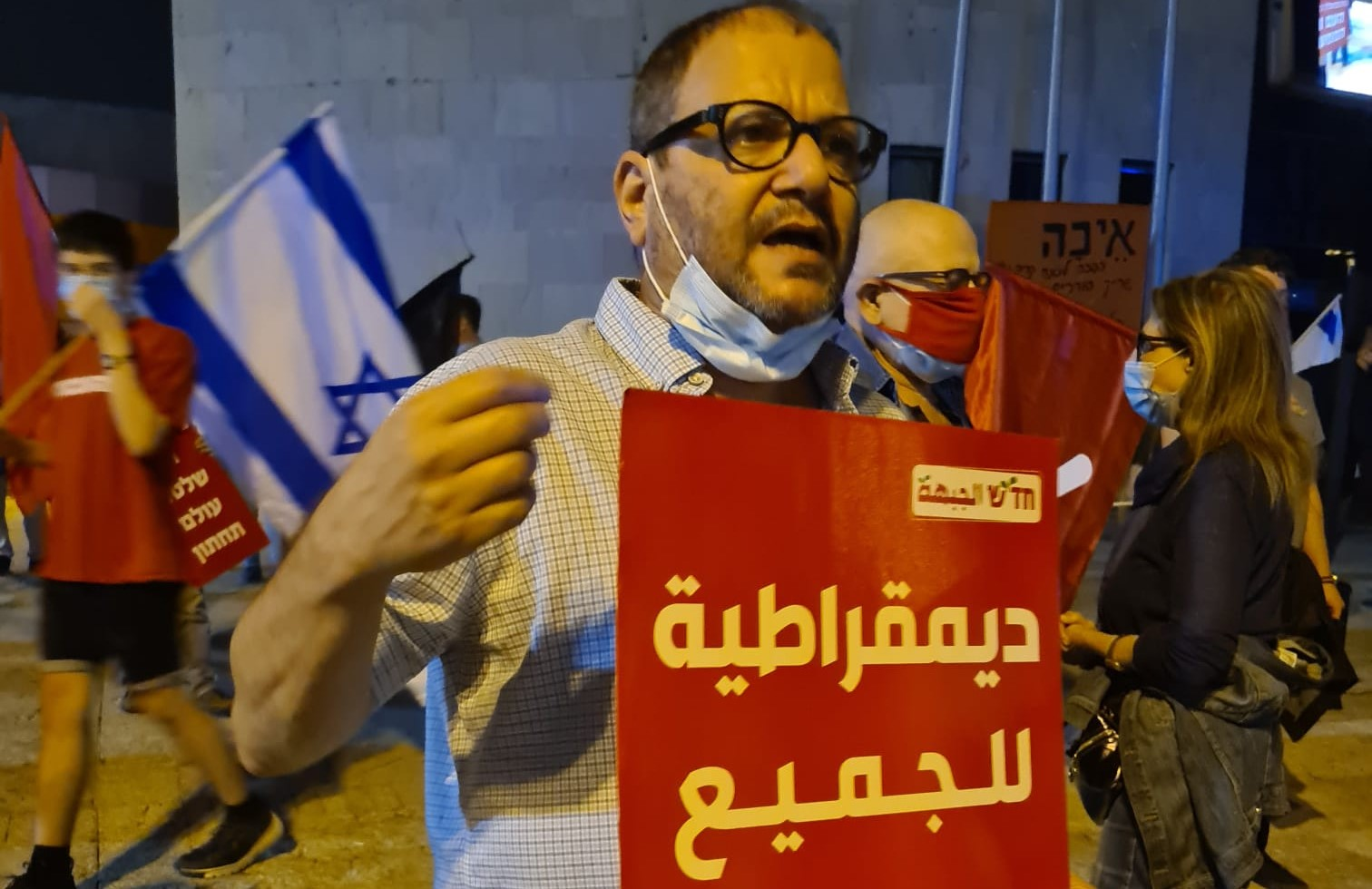 """Hadash MK Ofer Cassif (Joint List) at the anti-Netanyahu protest held in Holon, south of Tel Aviv, on Saturday evening, November 7. The Hadash sign reads in Arabic: """"Democracy for All."""""""