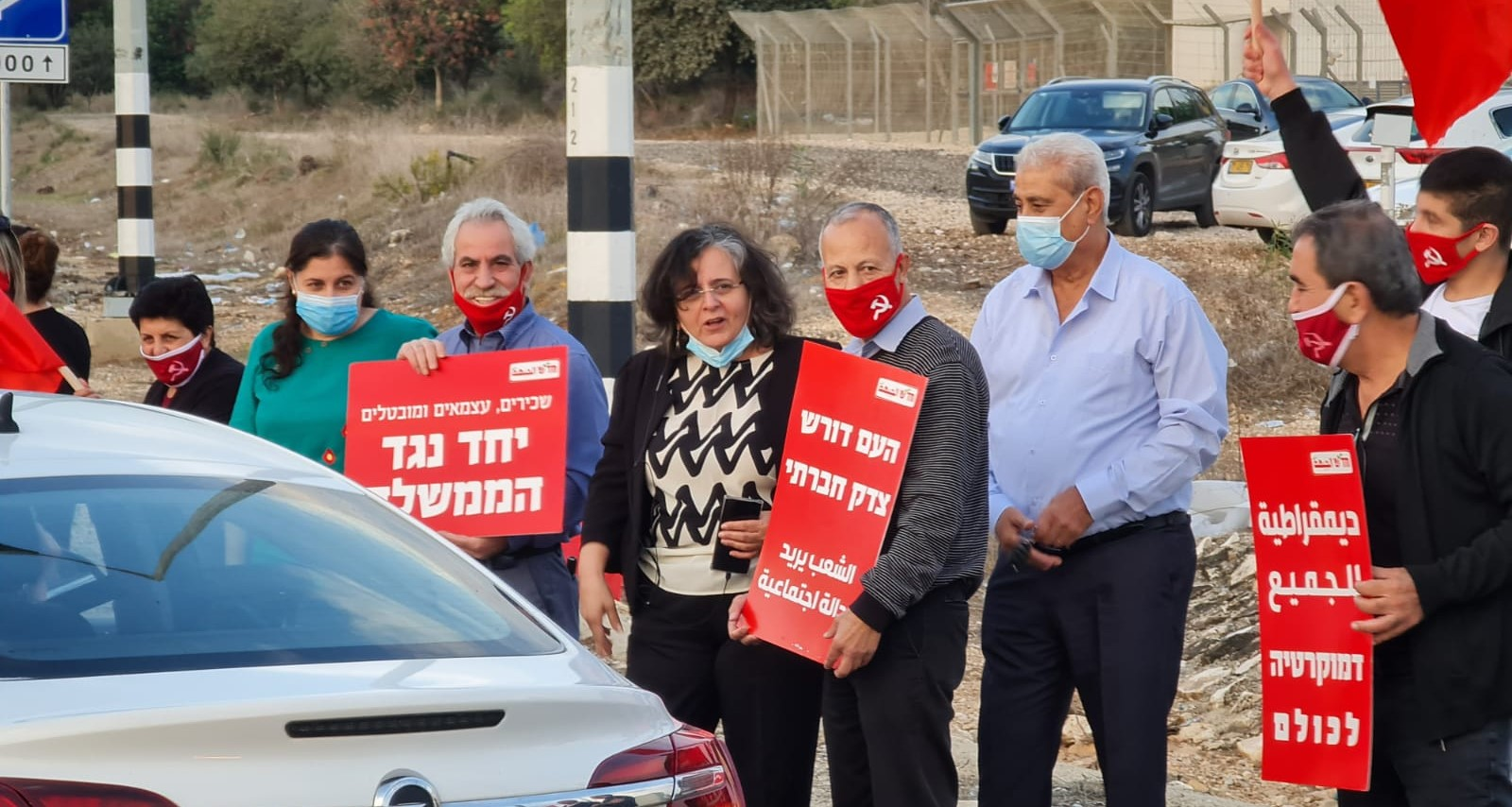 "Members of Hadash and the Communist Party of Israel demonstrate at the Acre junction against Netanyahu's far-right government , Saturday, November 7. Among the demonstrators: Joint List MK Aida Touma-Sliman (center) and next to her wearing the red ""hammer and sickle"" mask and holding the sign ""The people demand social justice,"" former Hadash MK Dr. Abdullah Abu Maaruf; next to him in the light blue shirt and mask, MK Jaber Asaqla. Other Hadash signs read: ""Employees, Independents and Unemployed – Together against the government"" and ""Democracy for All."""
