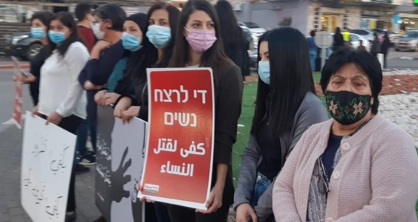 """Demonstrators in Arrabe protest violence against women following the murder of a resident of the city by her ex-husband, Tuesday, November 17, 2020. The red Hadash placard in Hebrew and Arabic reads """"Enough murdering of women."""""""