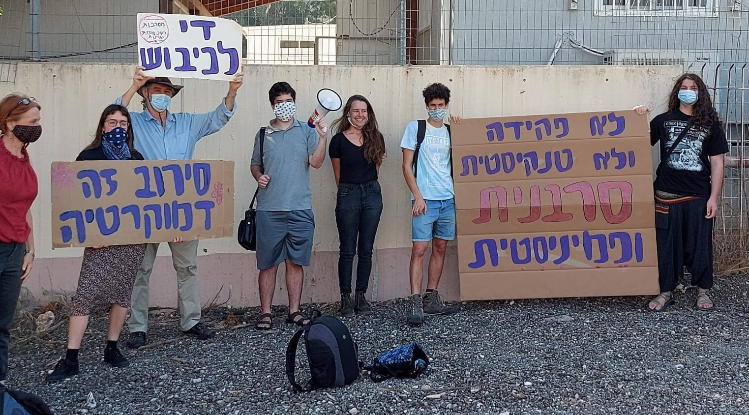 "Demonstrators express solidarity with Hallel Rabin (center, wearing black) outside the Tel Hashomer military induction center near Tel Aviv, October 21, 2020. The large placard at the right reads: ""Not as a clerk and not in a tank – Rather a refuser and feminist""; at the left the sign held aloft reads ""End the occupation""; and the placard below it reads: ""Refusal is democracy."""
