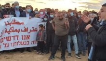 "Hadash MK Youssef Jabareen (Joint List), right, addresses a protest held in the Negev against land expropriation, November 26, 2020. The white banner reads in Arabic and Hebrew: ""Our Demand – Recognition of Our Ownership of Our Lands."""