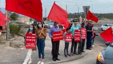 """Hadash and Communist Party activists conduct a """"red flag protest"""" in the Galilee. From left to right the Hadash placards read: """"The people demand social justice""""; """"Netanyahu serves the wealthy""""; """"Salaried, independents, and unemployed together against the government""""; """"Democracy for all."""""""
