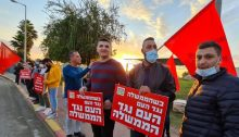 "Members of Hadash hold a ""Red flag protest"" against Netanyahu near the Arab town of Taybe in the south of the Triangle region. The placards in the foreground read: ""When the government is against the people, the people are against the government."""