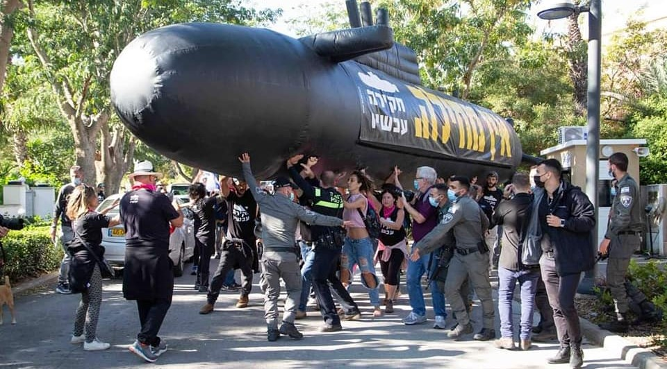 """Police and demonstrators scuffle on Friday afternoon, December 25, near the private residence of Benjamin Netanyahu in Caesarea. The banner on the plastic submarine reads: """"No Absolution – Investigate Now."""""""