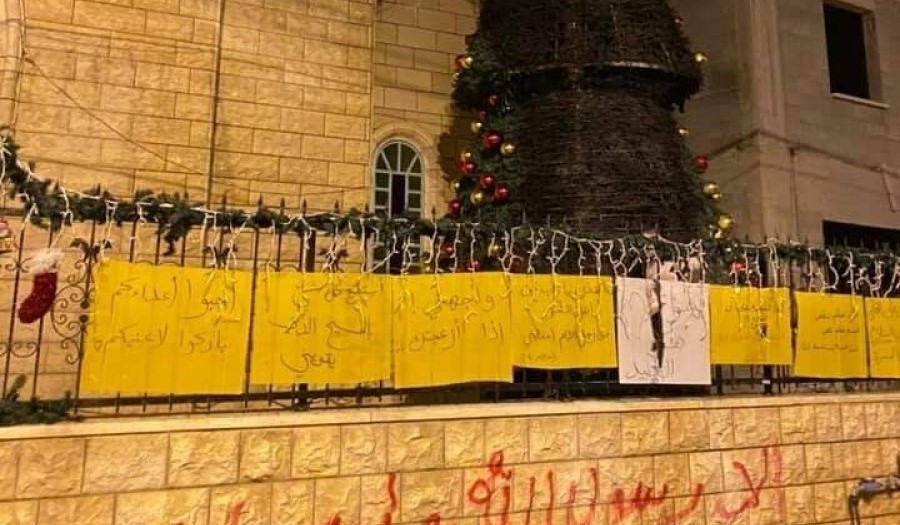 """The second Christmas tree to be burned outside the Catholic church in Sakhnin this week; the graffiti sprayed in red paint on the stone wall reads: """"Only Allah's Messenger Mohammed."""""""