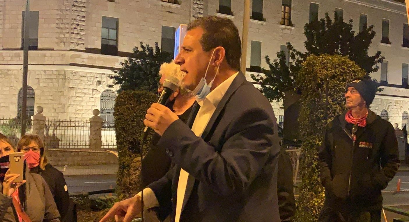 Joint List leader MK Ayman Odeh (Hadash) addresses protestors near the PM's official residence in Jerusalem, Saturday night, January 2, 2021.