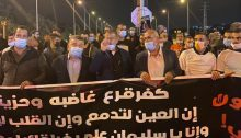 "Hundreds march in protest along Route 65 in Wadi Ara following the murder of Sliman Naziye Masarweh, 25, a resident of the town, Wednesday, January 6, 2021. Hadash MK Youssef Jabareen, second from left, was among the protestors. In part, the banner reads: ""Kafr Qara is angry and saddened; our eyes are full of tears and our hearts [illegible]… and that O Sliman, … [illegible]"""