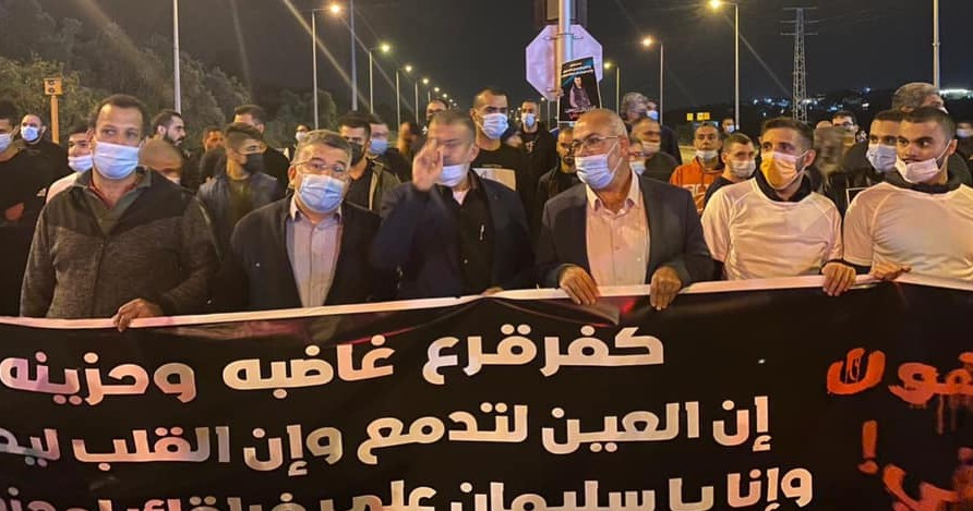 """Hundreds march in protest along Route 65 in Wadi Ara following the murder of Sliman Naziye Masarweh, 25, a resident of the town, Wednesday, January 6, 2021. Hadash MK Youssef Jabareen, second from left, was among the protestors. In part, the banner reads: """"Kafr Qara is angry and saddened; our eyes are full of tears and our hearts [illegible]… and that, O Sliman, … [illegible]"""""""