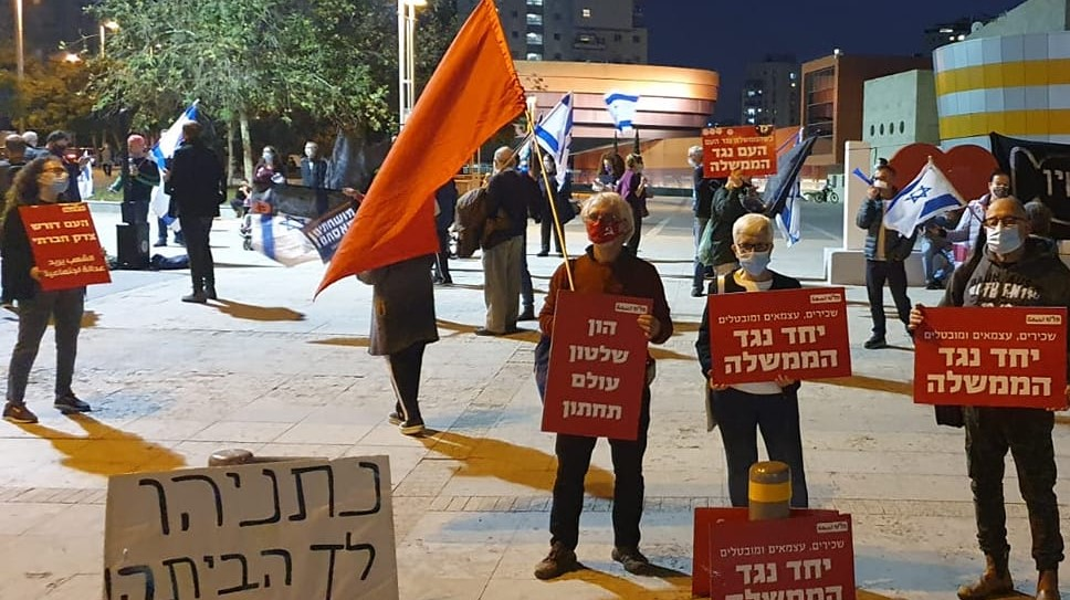 """Protesters against the far-right government gathered Saturday eveing, January 9, in the Meditech Plaza in Holon, south of Tel Aviv, among them members of the Communist Party of Israel including former Hadash MK Tamar Gozansky (second from right). The placard at the lower left reads: """"Netanyahu Go Home!"""" The red Hadash placards read (at extreme right) """"Salaried workers, independents and unemployed together against the government""""; (in the center) """"Capital, rule and underworld""""; """"(and at the extreme left) """"The people demand social justice."""""""