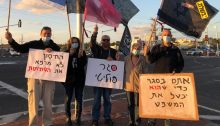 "Demonstrators protest against Netanyahu at an intersection near Haifa, Saturday, January 16, 2021. From left to right the signs read: ""The vaccine doesn't cure corruption,"" ""Political lockdown,"" and ""You're in lockdown so that he can suspend the trial."""