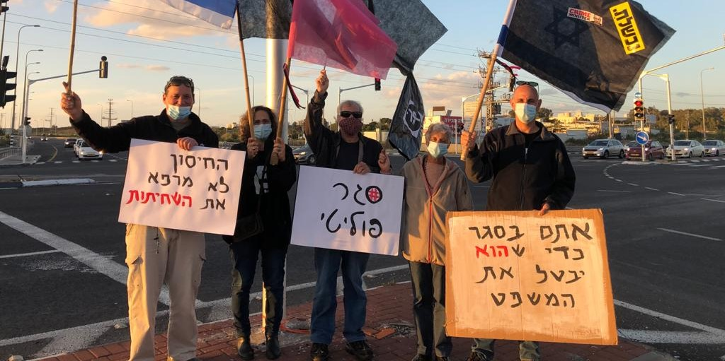 """Demonstrators protest against Netanyahu at an intersection near Haifa, Saturday, January 16, 2021. From left to right the signs read: """"The vaccine doesn't cure corruption,"""" """"Political lockdown,"""" and """"You're in lockdown so that he can suspend the trial."""""""