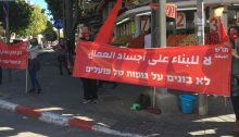 """Hadash and CPI activists protest in south Tel Aviv against the wanton non-enforcement of safety regulations that prevails in the construction industry in Israel, Friday, January 22, 2021. The banners in Arabic and Hebrew read """"No to construction over the bodies of workers"""" and (at left) """"The blood of construction workers is the fault of the government."""""""