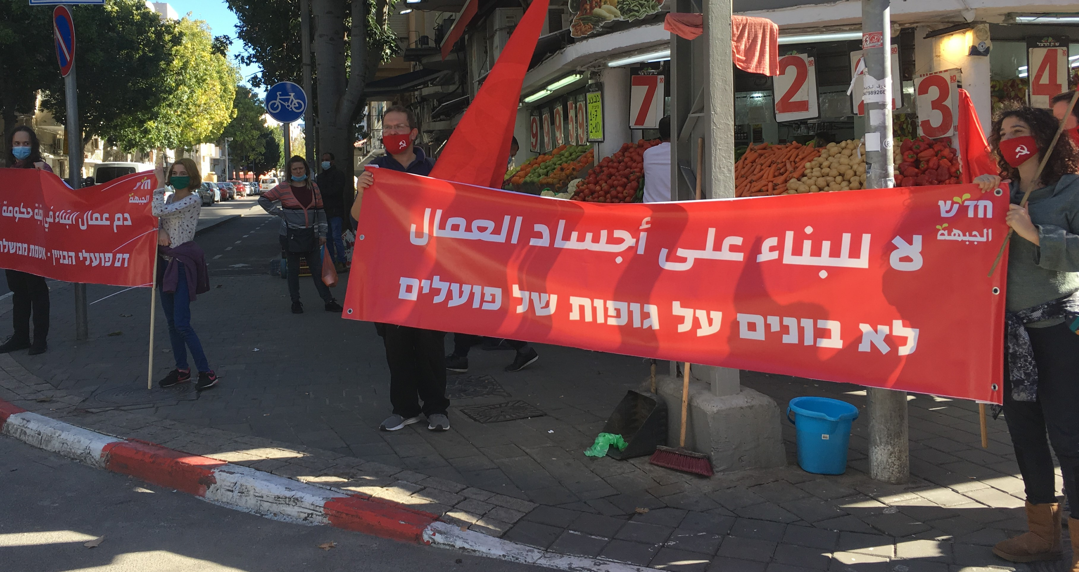 "Hadash and CPI activists protest in south Tel Aviv against the wanton non-enforcement of safety regulations that prevails in the construction industry in Israel, Friday, January 22, 2021. The banners in Arabic and Hebrew read ""No to construction over the bodies of workers"" and (at left) ""The blood of construction workers is the fault of the government."""