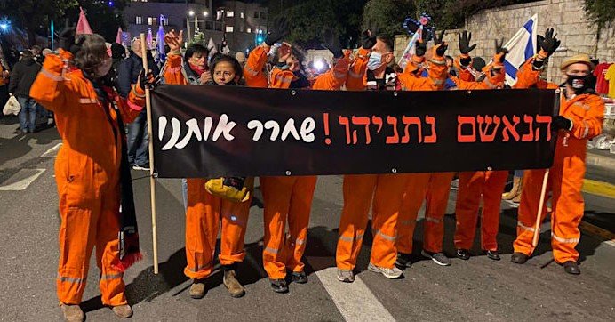 """Protesters near Jerusalem's Paris Square on Saturday, January 23, demonstrate against the continuing rule of far-right Prime Minister Benjamin Netanyahu. The sign reads: """"The accused Netanyahu! Set us free."""""""
