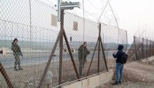 Two Israeli women soldiers stop a Palestinian worker as he tries to cross to his place of work in Israel through a hole in the fence near the city of Qalqilya, occupied West Bank, January 10, 2021.