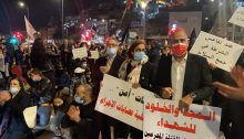 """Hundreds block the entrance to Nazareth on Friday night, February 5, 2021. First from right: Hadash secretary, Mansour Dahamshe; next to him are two Joint List MKs from Balad: Heba Yazbak and Mtanes Shehadah; among the placards: """"Glory and eternity to the martyrs""""; """"Against police inaction in collecting arms."""""""