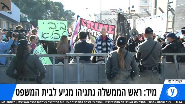 """Protesters call for Prime Minister Benjamin Netanyahu's resignation on Monday, February 8, outside the Jerusalem courthouse where his trial is about to resume. The caption beneath the live broadcast image reads: """"Prime Minister Netanyahu is about to arrive at court."""""""