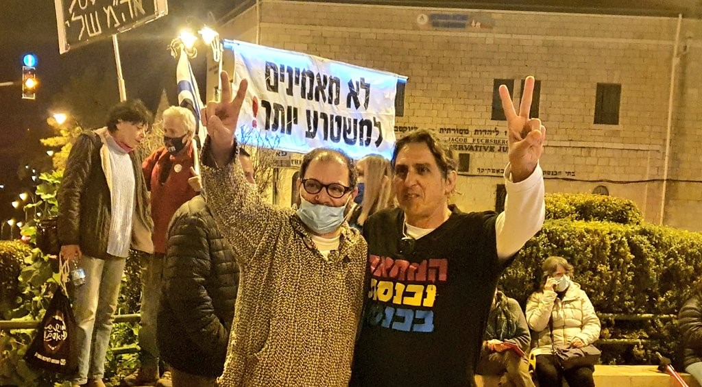 """Hadash MK Ofer Cassif (Joint List, left) and leading protest activist Sadi Ben-Shitrit demonstrate near the official residence of the prime minister in Jerusalem's Paris Square, Saturday evening, February 13, calling for Netanyahu's resignation. The banner held up in the background reads """"We no longer believe this evil regime!"""""""