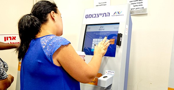 A newly unemployed woman enters details of her recent dismissal from work via a dedicated monitor in an Employment Service office.