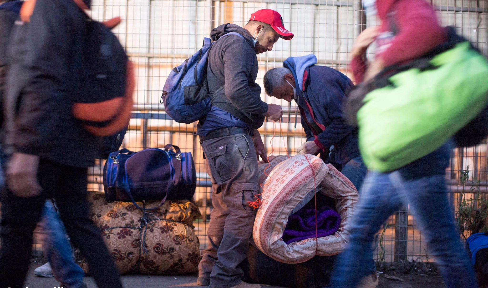 Palestinian workers from the occupied West Bank cross the Eyal Checkpoint, near Qalqilya, in the early morning hours to reach their workplaces in Israel – January 2021.