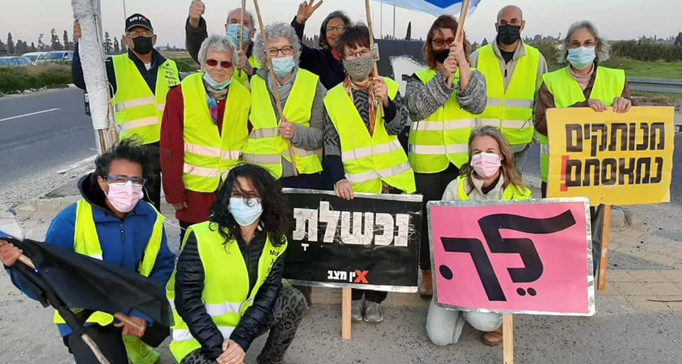 """Anti-Netanyahu protesters, late Saturday afternoon, February 27, near Hadera; from right to left the signs read: """"Detached, Enough of You!"""", """"Go,"""" """"You Failed."""""""