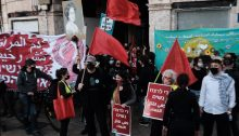 "Demonstrators gather in Jaffa on Saturday, March 6, to commemorate today's International Women's Day. The two placards in the foreground read: ""Enough murder of women""; the large banner to the left reads: ""Women's blood is not cheap."""