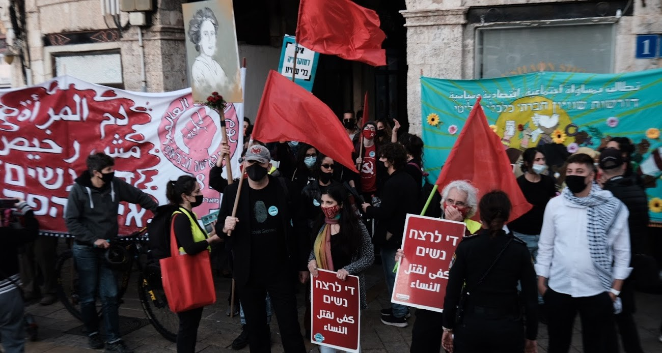 """Demonstrators gather in Jaffa on Saturday, March 6, to commemorate today's International Women's Day. The two placards in the foreground read: """"Enough murder of women""""; the large banner to the left reads: """"Women's blood is not cheap."""""""