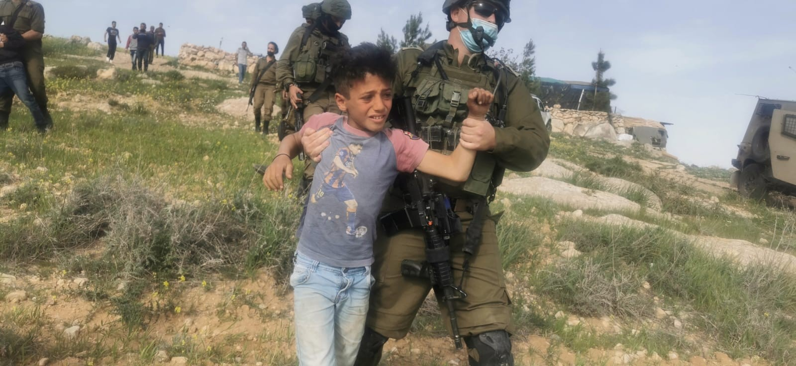 An Israeli soldier detains a Palestinian child close to al-Rakiz in the south Hebron hills, Wednesday, March 10, 2021.