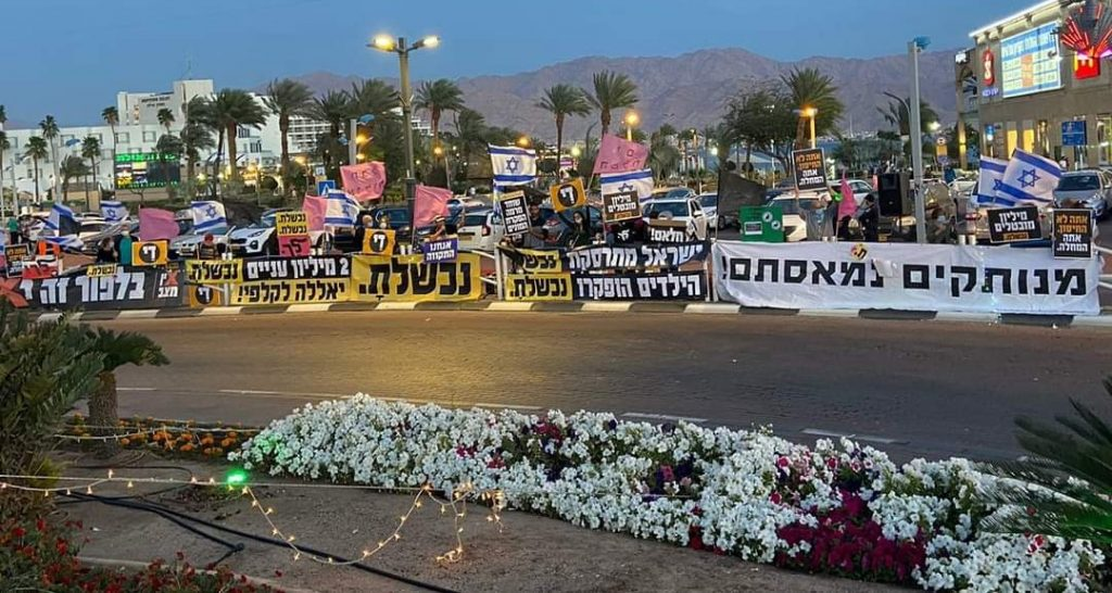 Anti-Netanyahu protesters demonstrate in the southern city of Eilat, near the Red Sea, Saturday evening, March 13, 2021.