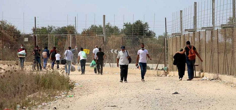 Palestinian workers enter and exit Israel through a gap in the Security Barrier.