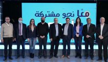"""Ma'an party leader Ahmad Darawsheh, center, stands alongside Hadash MK Ayman Odeh, head of the Joint List, and a group of other leaders from the alliance. The slogan in the background reads """"Together towards unity."""""""