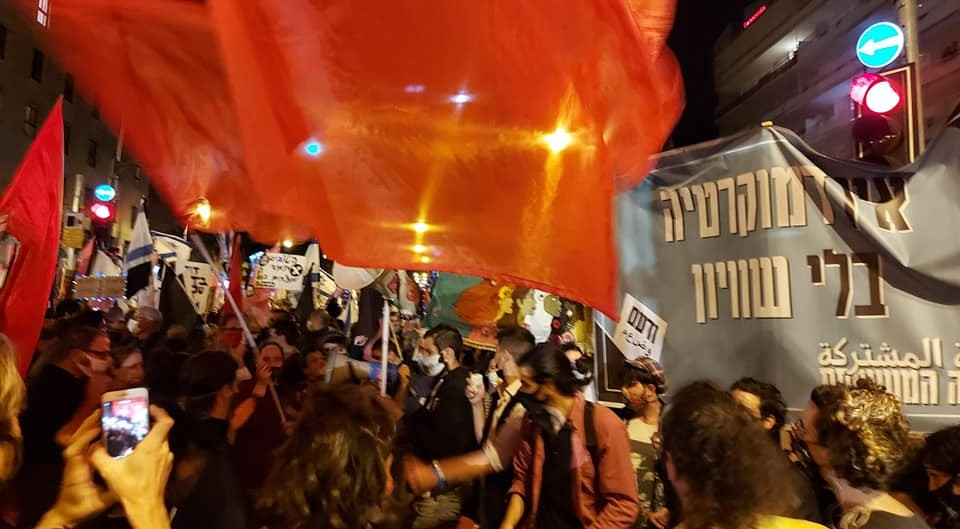 Hadash and Communist Party of Israel activists brandish red flags and Joint List banners during the mass protest held in Jerusalem against far-right Prime Minister Benjamin Netanyahu, Saturday night, March 20, 2021.