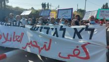 "Activists demonstrate alongside local residents against the planned evictions of Palestinian refugee families living since 1956 in the occupied East Jerusalem neighborhood of Sheikh Jarrah, Friday, April 16, 2021. The large banner reads in Hebrew and Arabic ""No to the displacement of families."" An Arabic placard held aloft to the right of center says ""Diplacement is a war crime."""