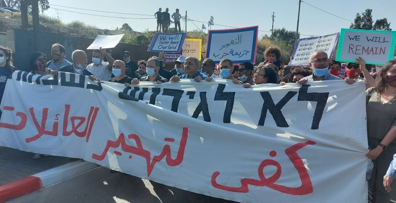 "Activists demonstrate alongside local residents against the planned evictions of Palestinian refugee families living since 1956 in the occupied East Jerusalem neighborhood of Sheikh Jarrah, Friday, April 16, 2021. The large banner reads in Hebrew and Arabic ""No to the displacement of families."" An Arabic placard held aloft to the right of center says ""Displacement is a war crime."""