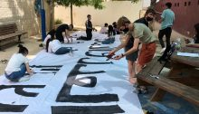 """Preparing for a mass demonstration for Jewish-Arab solidarity and coexistence, pupils from the Yad b'Yad school in Jerusalem paint a huge banner in Hebrew and Arabic: """"Equality and security for all Jerusalem residents."""""""