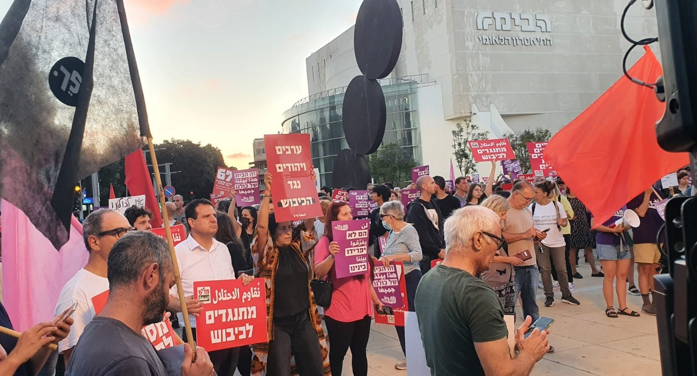 """Joint List chair MK Ayman Odeh (third from left, with a Hadash placard – """"Opposing the Occupation"""") at the protest in Habima Square in Central Tel Aviv, Saturday evening, May 15"""