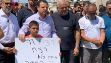 """MK Ayman Odeh (second from left) during the protest held in Lod last Friday, May 28, 2021. The headline on the white placard reads: """"Murder is murder."""""""