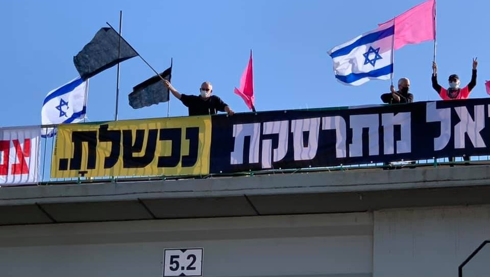 """Anti-Netanyahu protestors demonstrate from atop a highway overpass near Hadera, Saturday, May 29, 2021. The banners read: """"Israel is crashing"""" and """"You have failed."""""""