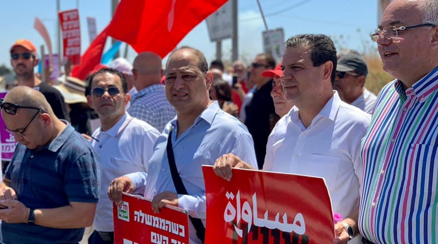 """MK Ayman Odeh (second from right) during an anti-Netanyahu protest held at Kohav Yair Junction, May 14, 2021; the placard Odeh's holding reads """"Equality."""""""