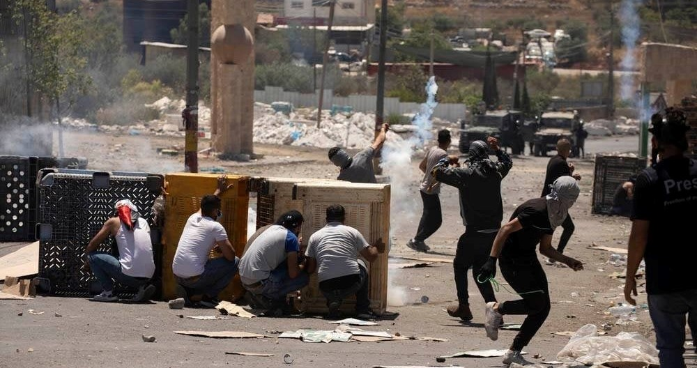 Palestinians clash with Israeli occupation forces during a protest in the West Bank village of Beita against a new Israeli settler outpost named Evyatar recently erected on Palestinian land on a mountain adjacent to the village, June 18, 2021.