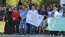 """All three Hadash MKs, Aida Touma-Sliman, Ofer Cassif and Ayman Odeh (third to fifth from left), attend the rally against the renewal of the racist Citizenship Law that was held on Tuesday, June 29 outside the Knesset in Jerusalem. The white sign held by Odeh reads in Hebrew: """"The Citizenship Law – Collective Punishment."""" The Arabic sign held by the two girls at the right reads """"Enough injustice – Ours is a humanitarian cause par excellence – Down with the law preventing reunification!"""""""