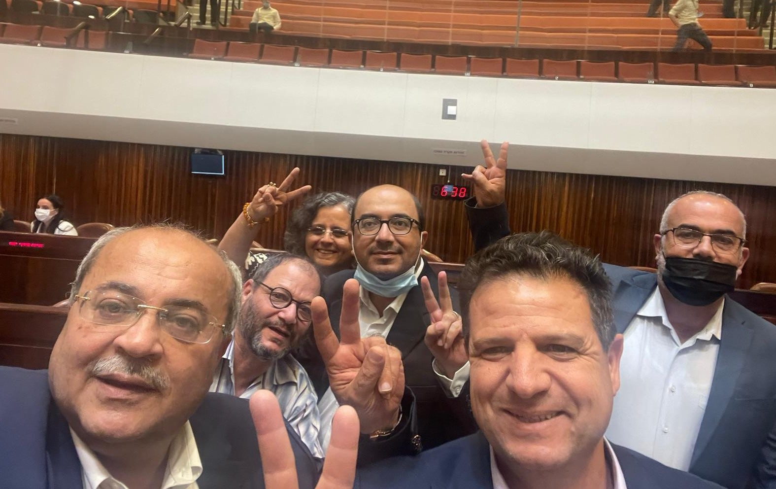 """The Joint List's six MKs pose in the plenum for a picture commemorating the defeat of another annual extension to the """"emergency measure"""" statue of Israel's racist Citizenship Law, Tuesday, July 6, 2021."""