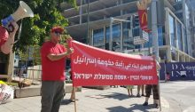 """Hadash activists demonstrate outside a major Tel Aviv construction site, Friday, July 2, where Mosab Al-Nagabi from Hebron in the occupied West Bank was killed in a work accident on June 20, 2021. The Hadash banner reads in Arabic and Hebrew: """"The blood of construction workers is the fault [""""on the neck""""] of the government of Israel."""""""