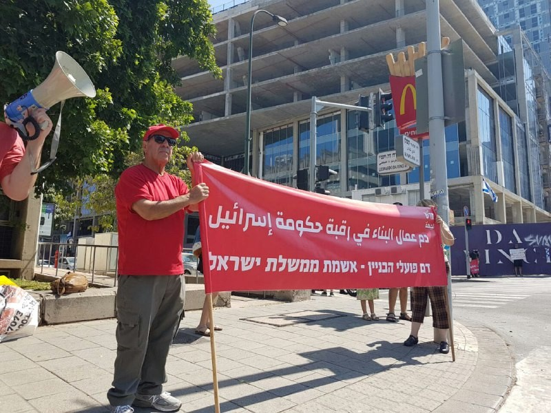 """Hadash activists demonstrate outside a major Tel Aviv construction site, Friday, July 2, where Mosab Al-Nagabi from Hebron in the occupied West Bank was killed in a work accident on June 20, 2021. The Hadash banner reads in Arabic and Hebrew: """"The blood of construction workers is the fault [""""on the neck""""]of the government of Israel."""""""