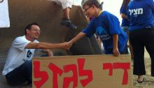 """Dov Khenin attends a demonstration against construction on the Palmahim beach along Israel's southern Mediterranean coast. The sign held by the boy reads """"Enough Robbery."""""""