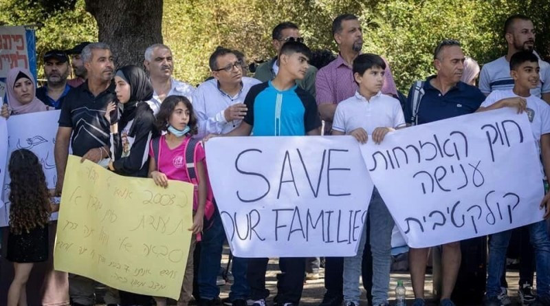 """Demonstrators protest outside the Knesset against the Citizenship and Entry into Israel Law, July 6, 2021. The Hebrew sign to the right reads: """"The Citizenship Law constitutes collective punishment."""""""
