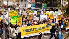 """Climate activists stage a rally in Central Tel Aviv, February 15, 2021. The large yellow banner emphasizes: """"NOW it's burning."""""""